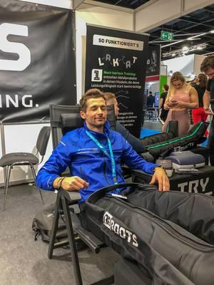 Mann relaxiert durch die regenerierende Massage von ReBoots auf Kölner Fitnessmesse