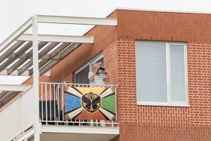 Mann schaut mit Fernglas aus einem Balkon, auf dem eine Flagge mit dem Logo von Tomorrowland Festival aufgehängt ist