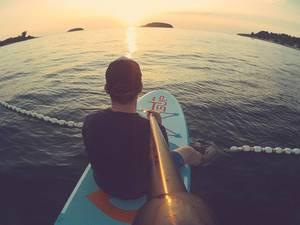 Mann schaut sich den Sonnenuntergang auf einem Paddelbrett an