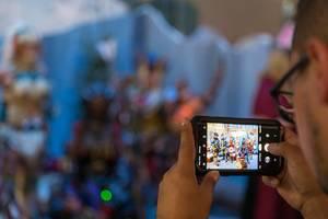Mann schießt ein Foto mit dem Smartphone von der Cosplayszene am Messestand von Monster Hunter World: Iceborne