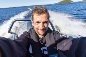 Mann schießt ein Selfie auf einem fahrenden Motorboot in blauem Gewässer des Päijännesees im Finnland-Urlaub