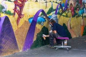 Mann sitzt auf einem Stuhl und sprüht Graffiti