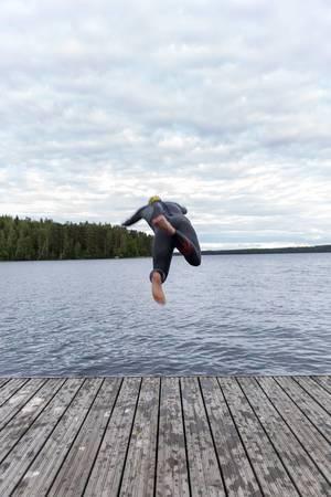 Mann springt ins Wasser durch einen großen Sprung von dem Bootssteg, um im finnischen See Päijänne schwimmen zu gehen