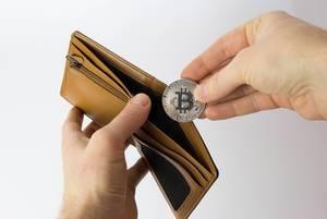 Mann steckt ein Bitcoin in seine Brieftasche