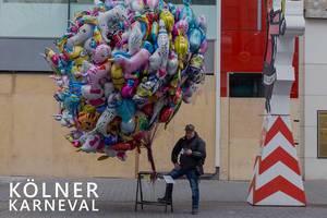 """Mann steht alleine neben vielen bunten Luftballons für Kinder, neben dem Bildtitel """"Kölner Karneval"""""""