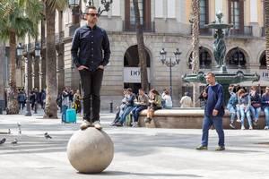 Mann steht auf einer Steinkugel neben dem Drei-Grazien-Brunnen am Placa Reial in der Katalonien-Provinz Barcelona, Spanien