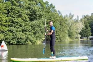 Mann steht mit Paddel auf einem Stand-Up Paddleboard und betreibt Wassersport auf einem See in Finnland