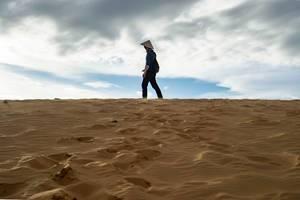 Mann steht oben auf den roten Sanddünen in Mui Ne, Vietnam vor leicht bewölktem Himmel