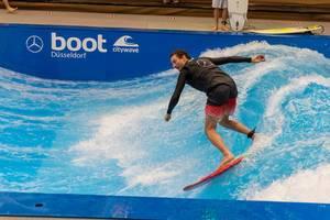 Mann surft und demonstriert stehende Welle mit kurzem Surfboard