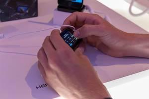Mann testet in Händen die neue Action Kamera GoPro Hero 7 an der Photokina in Köln