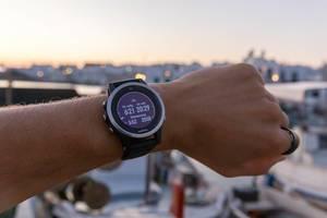 Mann trägt die Laufuhr von Garmin, mit Anzeige von Sonnenaufgang, Sonnenuntergang und Dämmerungszeit
