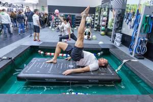 Mann trainiert an einem ReaxBoard - ein neues Neuromuskuläres Trainingsgerät an der Fibo-Messe in Köln