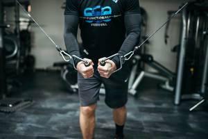 Mann trainiert Brustmuskeln durch Zug an Federn eines Kreuzzuggeräts