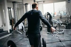 Mann trainiert seine Brustmuskeln mit Gerät in Fitnessstudio