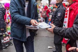 Mann verteilt Flyer für eine autofreies Stadt beim Rosenmontagszug in Köln