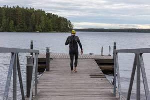 Mann von hinten mit Neoprenanzug und Tauchbrille auf einem Holzsteg am Päijännesee in Finnland