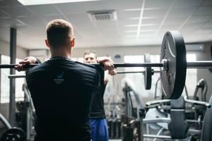 Mann vor Spiegel in Ausgangsposition für Gewichtheben mit Langhantel