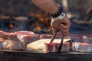 Mann wendet Kotelett auf Grillplatte mit Grillzange und trägt Armband vom Tomorrowland Festival 2019