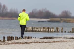 Mann with reflecting yellow sports jacket running on a beach near Beach Resort Makkum