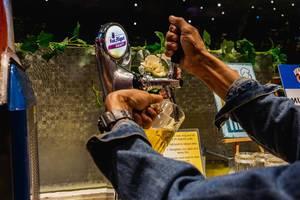 Mann zapft sich Fassbier in ein Glas