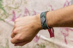 Mann zeigt das Tomorrowland Festival-Armband an seiner Hand mit dem Logo des Festivals