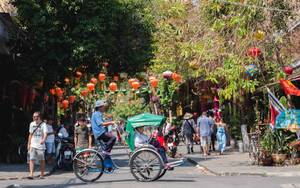 Männer auf einem Fahrrad auf einer geschmückten Straße der Küstenstadt Hoi Ann, Vietnam