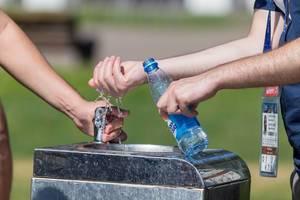 Männer befüllen am Trinkbrunnen eine Flasche mit Wasser