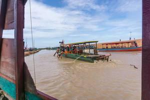 Männer helfen einem Boot dass auf einer Sandbank fest steckt in Siem Reap