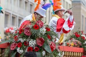 Männer im Wagen des Festkomitee des Kölner Karnevals 1823 werfen den Zuschauern Blumen zu - Kölner Karneval 2018