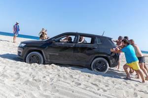 Männer schieben einen SUV auf dem Strand an