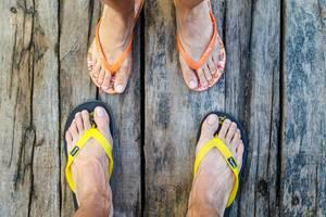 Männer- und Frauenfüße in Flip-Flops stehen sich gegenüber auf Holzboden