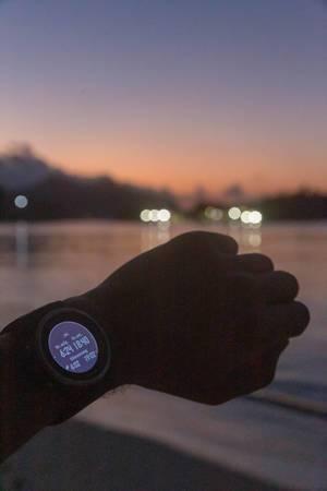 Männerarm mit Garmin Fenix 5S Smartwatch, die Sonnenaufgang, Sonnenuntergang und Dämmerung im Constance Ephelia Resort auf Mahé, Seychellen, anzeigt