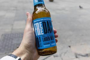"""Männerhand hält alkoholfreies Lagerbier """"Free Damm"""" aus Malta"""