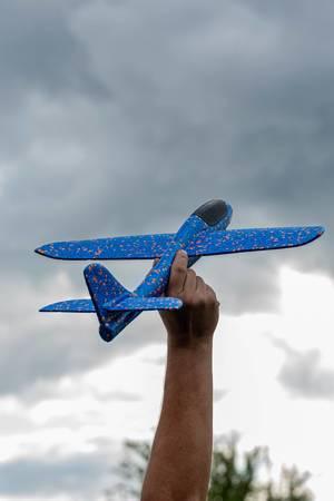 Männerhand hält ein blau-oranges Spielzeug- und Modellflugzeug in die Luft, mit dunklen Wolken im Hintergrund
