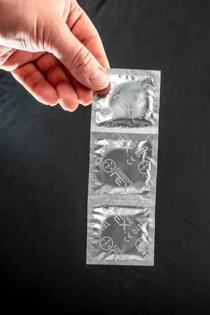 Männerhand hält einen Streifen mit verpackten Kondomen vor schwarzem Hintergrund