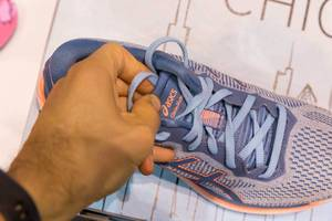 Männerhand zieht am blauen Schnürsenkel der Laufschuhe GlideRide von asics