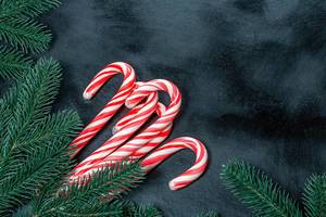 Many Christmas candy canes with Christmas tree branches on a black background (Flip 2019)