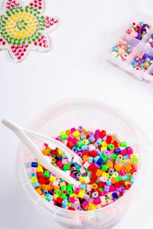 Many little beads with tweezers on white background (Flip 2019)