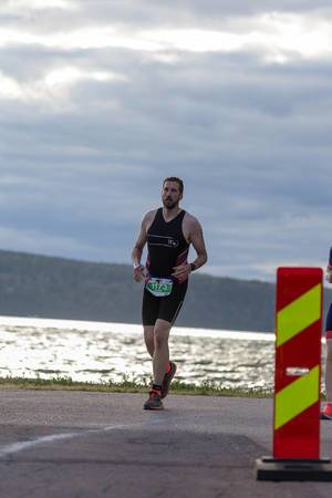 Marathon runner on the last meters of the Ironman competition in Finland 2019, with a lake Vesijärvi in the background