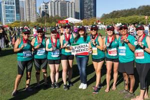 Marathonläuferinnen halten ein Transparent mit dem Fuerza Mexico Hashtag