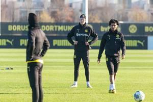 Marco Reus and Erling Haaland watch Mahmoud Dahoud as he walks towards the ball during a Borussia Dortmund training