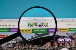 Mardi Gras logo on a laptop screen with a magnifying glass