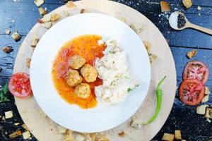 Marinierte Hackfleischbällchen mit Reis auf einem weißen Teller, Tomatenscheiben und grüner Chili