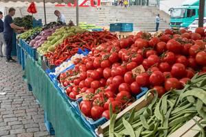 Marktstand mit Brechbohnen, Tomaten und anderem Gemüse