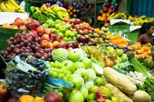 Marktstand mit einer reichen Auswahl an Früchten und Gemüse wie Bananen, Äpfel, Trauben, Kiwis, Orangen, Champignons und Kürbissen
