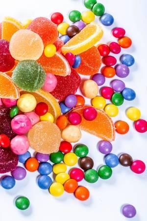 Marmelade elly und Pralinen von verschiedenen Farben auf weißem Hintergrund