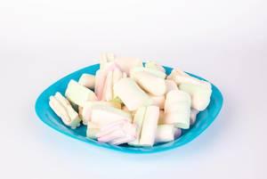 Marshmallows in Pastellfarben und verschiedenen Formen auf blauem Teller isoliert vor weiß