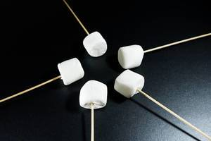 Marshmallows on sticks pointing to the center