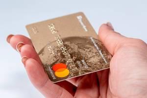 Mastercard - Kreditkarte in einer Frauenhand, vor weißem Hintergrund