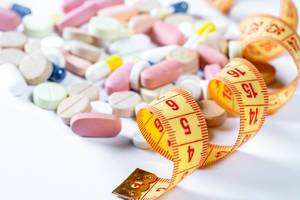 Maßband mit assortierten Tabletten und Medikamenten – Nahrungsergänzung und Diätpillen